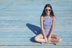 Just smile!. Smiling teenager girl sitting on the beach on the bright background Stock Images