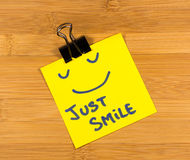 Just smile sticky note on wooden background Royalty Free Stock Photography
