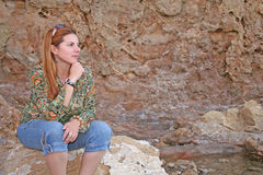 Just thinking. Young woman sitting on a rock, thinking Royalty Free Stock Images