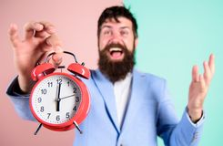 Just in time. Man bearded happy cheerful businessman hold alarm clock. Timely concept. Hipster happy working day is over royalty free stock photos