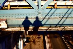 Just the two of us. Father and son overlooking there shadow projected on bridge royalty free stock image