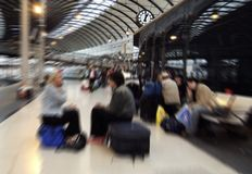 Just waiting. Zoom blurred image of people waiting for trains on Newcastle-upon-Tyne central station, UK, the zoom centred on station clock showing one o'clock stock image