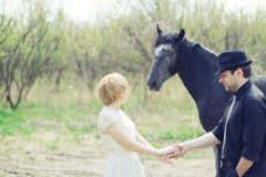 Just wedded young couple with horse dressed retro Royalty Free Stock Photos