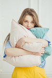 Just woken up girl without make up stands with pillows Stock Images