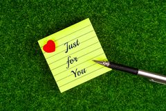 Just for you. In memo with heart shape and pen on grass background royalty free stock image