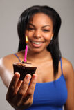 Just for you a party celebration cake with candle. Happy birthday. Beautiful young black girl, holding a chocolate cup cake out to the camera. A pink candle is Royalty Free Stock Photos