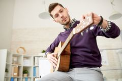 Justage der Gitarre im modernen Büro stockfoto