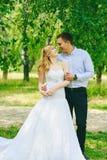 Juste couples affectueux mariés de hippie dans la robe de mariage et costume sur le champ vert dans une forêt au coucher du solei Photo stock