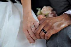 Juste couples interraciaux mariés tenant des mains portant des anneaux de mariage images stock