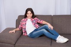 Juste détendant ici Sentez-vous confortable sur ce divan Fille d'enfant avec la longue détente de cheveux Endroit préféré pour dé images libres de droits