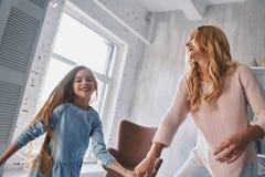 Juste danse ! Mère et fille tenant des mains et souriant tandis que image libre de droits