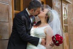 Juste jeunes baisers mariés de couples Photographie stock libre de droits