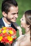 Juste jeunes mariés mariés heureux sur le fond d'herbe verte Photos stock
