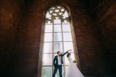 Juste la pose mariée devant la vieille cathédrale gothique de style a arqué la fenêtre avec le filigrane Photographie stock