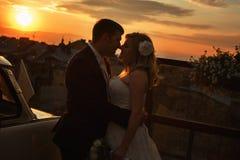 Juste le ménage marié se tient dans les lumières du coucher du soleil Photo stock