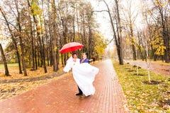 Juste les ménages mariés ont l'amusement sous le parapluie Photo libre de droits