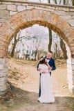 Juste les ménages mariés posent dans les portes du vieux mur baroque ruiné de château Photos libres de droits