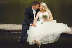 Juste les ménages mariés rient tout en se reposant avec les jambes croisées sur un b Images libres de droits