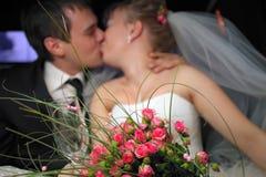 Juste ménages mariés embrassant dans la limousine Photographie stock libre de droits