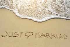 Juste marié écrit sur la plage de sable près de la mer Photos libres de droits