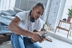 Juste se reposant Jeune homme africain beau choisissant la chanson sur salut Images libres de droits
