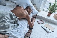 Juste se reposant Vue supérieure du jeune homme africain dormant tout en se trouvant Image libre de droits