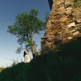 Juste support marié derrière un mur en pierre de château Image stock