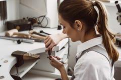 Juste un moment Vue de côté de bijoutier féminin préparant les outils pour le travail avec l'anneau argenté à son atelier de bijo photo stock