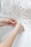 Justera bröllopsklänningcroset Fotografering för Bildbyråer