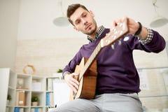 Justera gitarren på det moderna kontoret arkivfoto