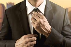 Justerar den iklädda dräkten för mannen och vitskjortan hans band royaltyfri fotografi
