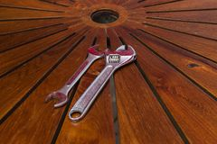 Justerbar skiftnyckel på trätabellen arkivfoton