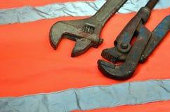 Justerbara och rörskiftnycklar mot bakgrunden av en orange signalarbetarskjorta Stilleben som förbinds med reparationen, järnväg Arkivfoton
