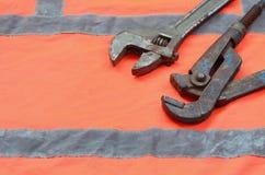 Justerbara och rörskiftnycklar mot bakgrunden av en orange signalarbetarskjorta Stilleben som förbinds med reparationen, järnväg Royaltyfri Bild