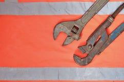 Justerbara och rörskiftnycklar mot bakgrunden av en orange signalarbetarskjorta Stilleben som förbinds med reparationen, järnväg Royaltyfria Foton