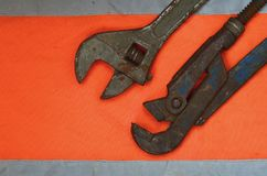 Justerbara och rörskiftnycklar mot bakgrunden av en orange signalarbetarskjorta Stilleben som förbinds med reparationen, järnväg Royaltyfri Fotografi