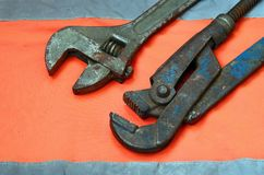Justerbara och rörskiftnycklar mot bakgrunden av en orange signalarbetarskjorta Stilleben som förbinds med reparationen, järnväg Royaltyfria Bilder