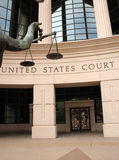 Justice. An arm holds the scales of justice in front of a US Court Building Stock Photo
