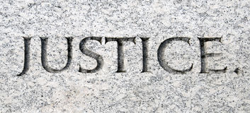 Justice. The word justice carved in stone stock photo
