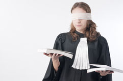Justice is blind. Young law school student holding statute books blindfolded with a scarf Stock Photography