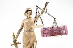 Justice is blind ( ... or maybe not ). Justice (greek:themis,latin:justitia) blindfolded with scales, sword and money on one scale. Corruption and bribing royalty free stock images