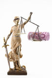 Justice is blind ( ... or maybe not ). Justice (greek:themis,latin:justitia) blindfolded with scales, sword and money on one scale. Corruption and bribing royalty free stock image