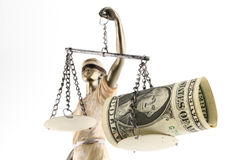 Justice is blind ( ... or maybe not ). Justice (greek:themis,latin:justitia) blindfolded with scales, sword and money (US dollar ) on one scale. Corruption and Stock Photography