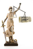 Justice is blind ( ... or maybe not ). Justice (greek:themis,latin:justitia) blindfolded with scales, sword and money (US dollar ) on one scale. Corruption and Royalty Free Stock Image