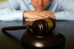 Justice concept. Man is sitting at the table opposite gavel royalty free stock photos