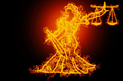 Justice on fire. Burning lady of justice on fire with black background Stock Image