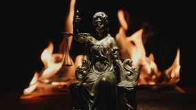 Justice in a fire trap - background. Lady justice or justitia goddess of Justice against the backdrop of a flaming fire in slow motion. Law concept with Themis stock video footage