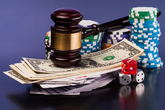 Justice and gambling money. Judge gavel and set of playing card with dices on reflective table Royalty Free Stock Images
