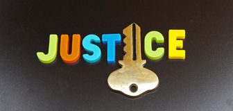 Justice holds the key. Text ' justice ' in colorful uppercase letters with the letter Stock Image