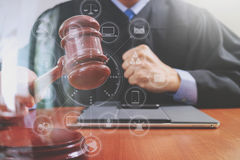 Justice and law concept.Male judge in a courtroom striking the g. Avel,working with digital tablet computer docking keyboard on wood table,virtual interface Royalty Free Stock Photo